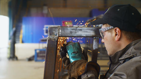 man in goggles and gloves grinds welding seam on carcass GIF