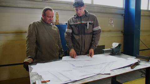 worker with colleague works with drawings at metal table GIF