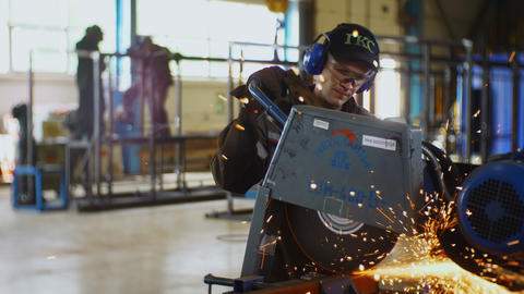 technician with headphones and goggles cuts metal part GIF