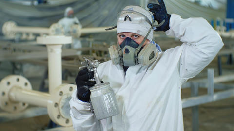 painter in protective suit takes off respirator in shop GIF