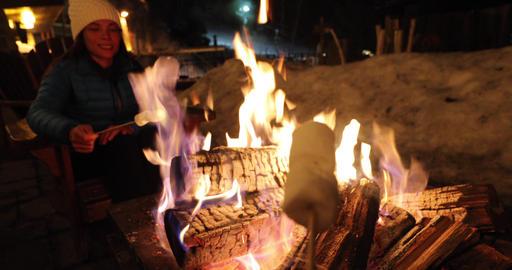 Winter holiday ski resort woman roasting marshmallows in BBQ firepit afterski ライブ動画