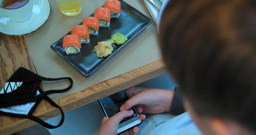 schoolboy makes photo of sushi in restaurant top view GIF
