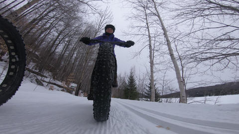 Fat bike in winter. Fat biker riding bicycle in the snow in winter. Close up Live Action