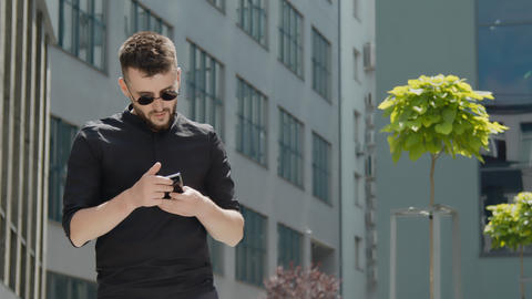 Portrait of a young businessman with glasses holding a mobile gadget receives an ライブ動画