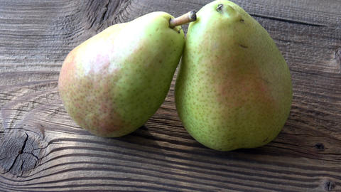 Two fresh pears on wooden table GIF
