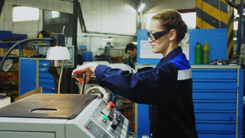 girl in uniform and goggles cleans milling machine at panel GIF