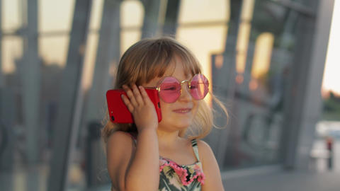 Tourist kid girl wearing stylish sunglasses use phone. Child using smartphone ライブ動画