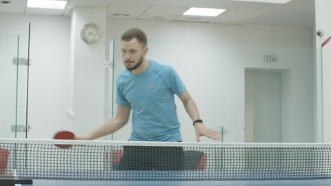 Portrait of concentrated bearded brunette sportsman playing table tennis in gym Acción en vivo