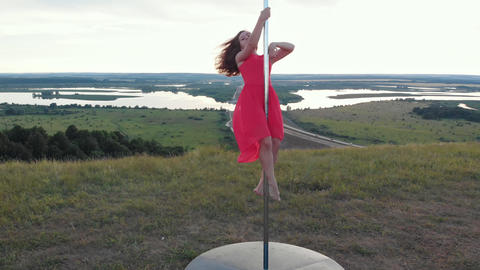 Young woman in pink dress dancing on the pole Acción en vivo