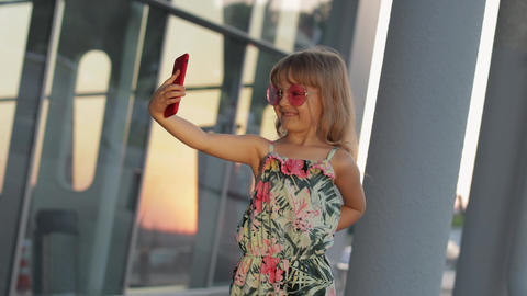 Tourist kid girl wearing trendy sunglasses use phone. Child using smartphone for ライブ動画