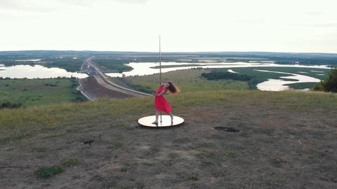 Young woman in pink dress dancing on the pole in nature Acción en vivo