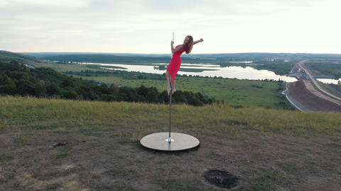 Young woman in pink dress dancing on the top of the pole in nature Acción en vivo