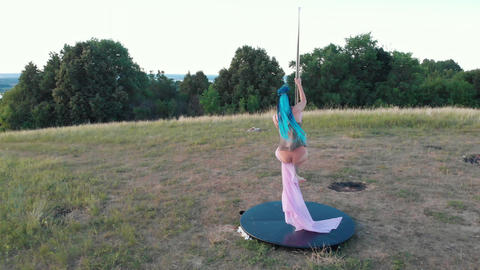 Woman with blue braids holding on the pole with pink veil outdoors Acción en vivo