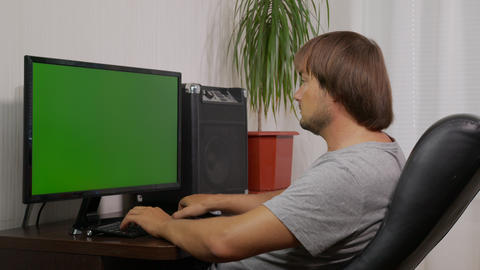 Shot of man typing on laptop keyboard with green screen, Working from home, Home Live Action