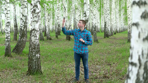 A young man is looking for the Internet in a birch forest. The man is in Live Action