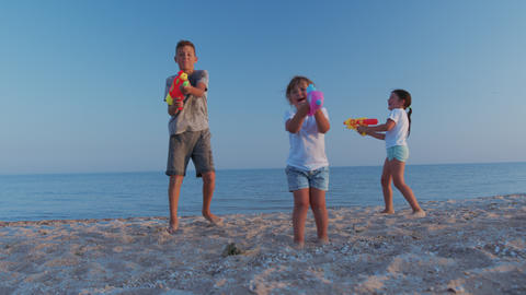 Little girls and boy on the sea. Children playing with water guns Acción en vivo