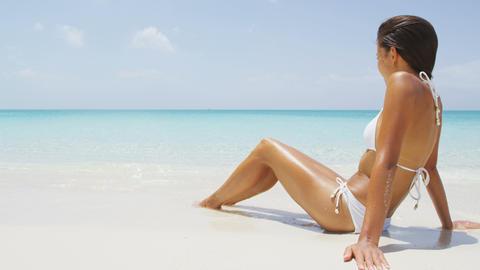 Sexy beach bikini body woman relaxing sun tanning at tropical luxury destination Live Action