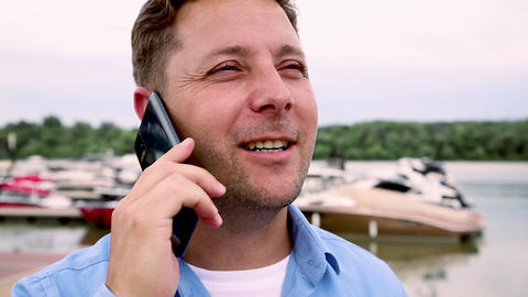 Man talking on the phone at port with Yachts and boats in background. Slow motion video in 60 fps GIF