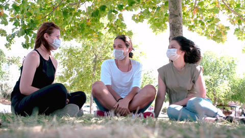 Young friends talking and laughing while sitting on grass. Meeting with friends in the park during Live Action