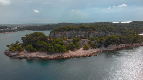 Flying around rocky cape on the shore of Adriatic Sea. Green forest and rocks of GIF