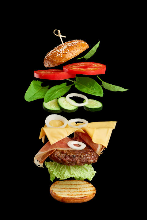 flying burger ingredients: cutlet, sesame seed bun, tomato, onion, green lettuce, cheese on black Photo