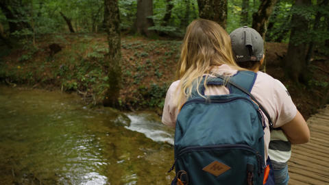 Woman and her kid look on a clear stream. Family walks in a green forest GIF