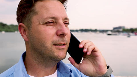Man talking on the phone at port by the river. Slow motion video in 60 fps GIF