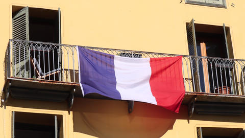 A three-colored French national flag flutters on the balcony Acción en vivo