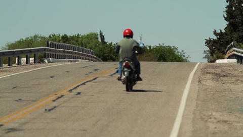 Motorcyclist with Red Helmet riding Motorcycle on Road. Back View Live Action