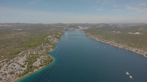 Aerial shot of a channel. Blue water between hilly shores. Sunny day in Croatia GIF