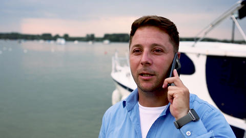 Man talking on the phone beside luxury yacht at port GIF