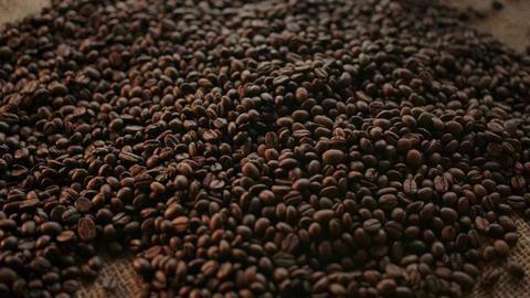 Human hands take a handful of roasted arabica dark coffee beans Acción en vivo