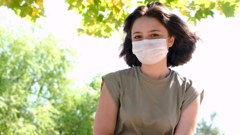 Portrait of lovely young happy woman with face mask. New normal after coronavirus outbreak. Healthy GIF