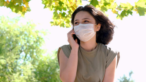 Young happy woman with face mask talking on the phone outside. New normal after coronavirus GIF
