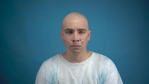 A bald young man with oncology sadly looks at the camera on a blue background Live Action