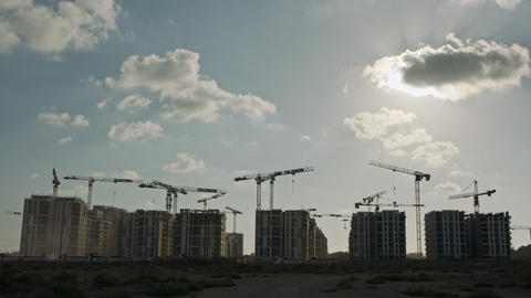 Timelapse of a large construction site with many cranes working over buildings GIF
