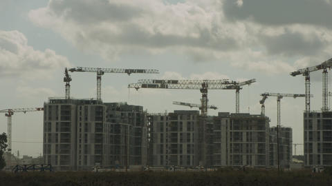 Timelapse of a large construction site with many cranes working over buildings Live Action