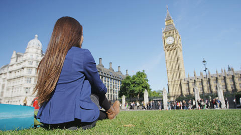 Woman relaxing on Parliament Square in London by Big Ben tourist attraction Live Action