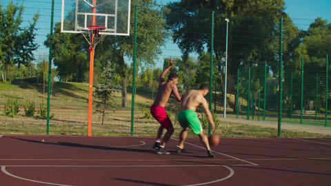 Shirtless athletic men playing streetball outdoors GIF