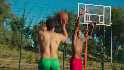 Basketball player making jump shot at urban court GIF
