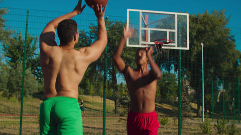 Fit basketball player blocking shot at urban court GIF