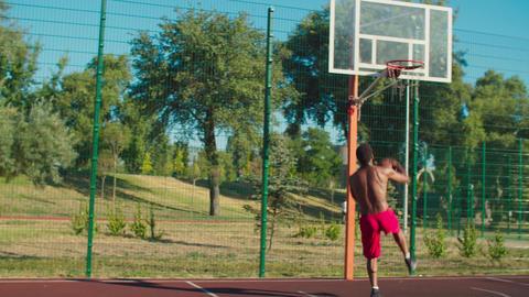 Shirtless basketball player slam dunking at court GIF