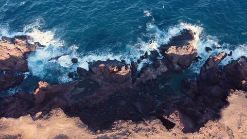 Drone flying along rocky beach. Beautiful coastline with waves. Aerial view of GIF