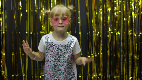 Stylish child dancing, make faces, waving hand in silly dance. Little blonde kid Live Action