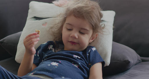 Portrait of a cute, funny little toddler girl at home eating a snack GIF