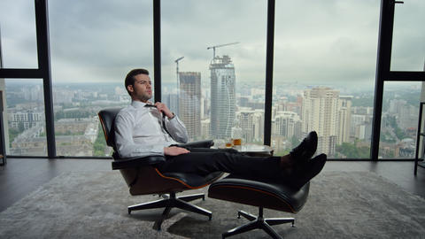 Businessman sitting on chair in modern interior. Professional adjusting tie Acción en vivo