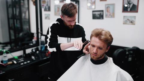 Hairdresser makes a stylish haircut to the client Acción en vivo
