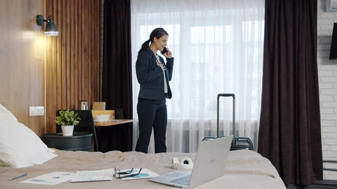Happy girl in suit calling from hotel talking on mobile phone and smiling Acción en vivo