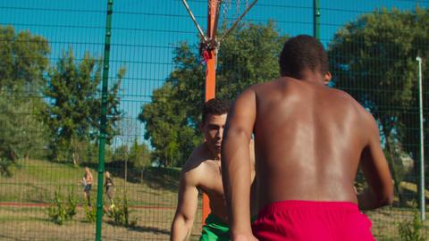 Two shirtless athletes playing basketball outdoor Acción en vivo