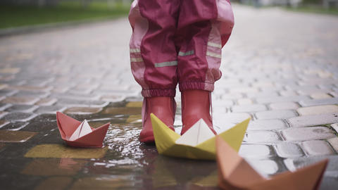 Feet of little girl in rubber boots stomping in puddle with paper boats around Live Action